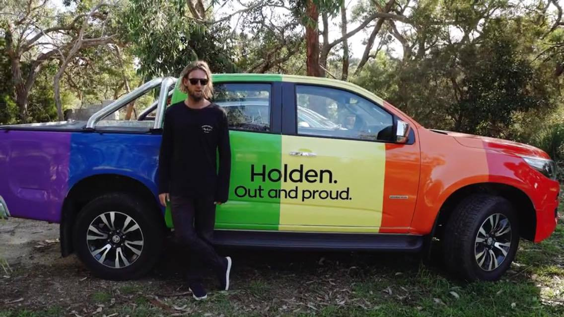 Wilko driving a rainbow car in Byron Bay